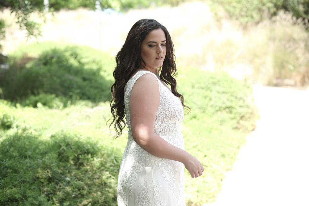 שמלת כלה מתחרה במידה גדולה, צמודה עם חגורת פנינים ומחשוף עמוק קיארה מבית סטודיו לבנה