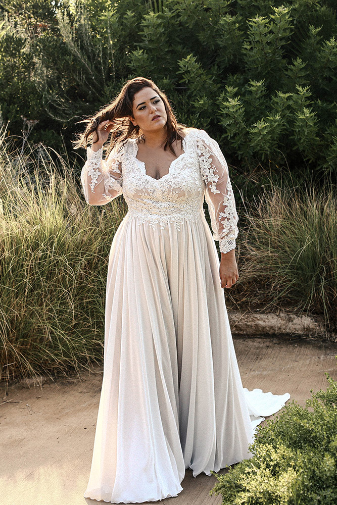 Darcy by studio levana plus levana plus size romanric wedding dress with baeded lace top love sleeves and a flowy shiffon skirt