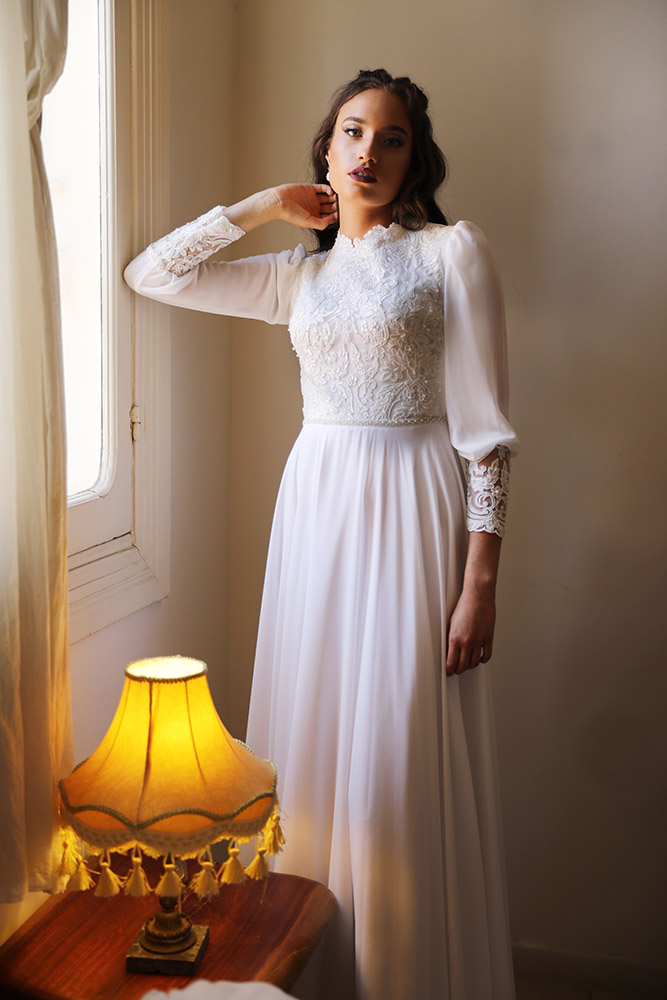 Kalla by studio levana modest weddong dress with baeds and sparkel lace top and a baeded belt long shher sleeves and high nackline