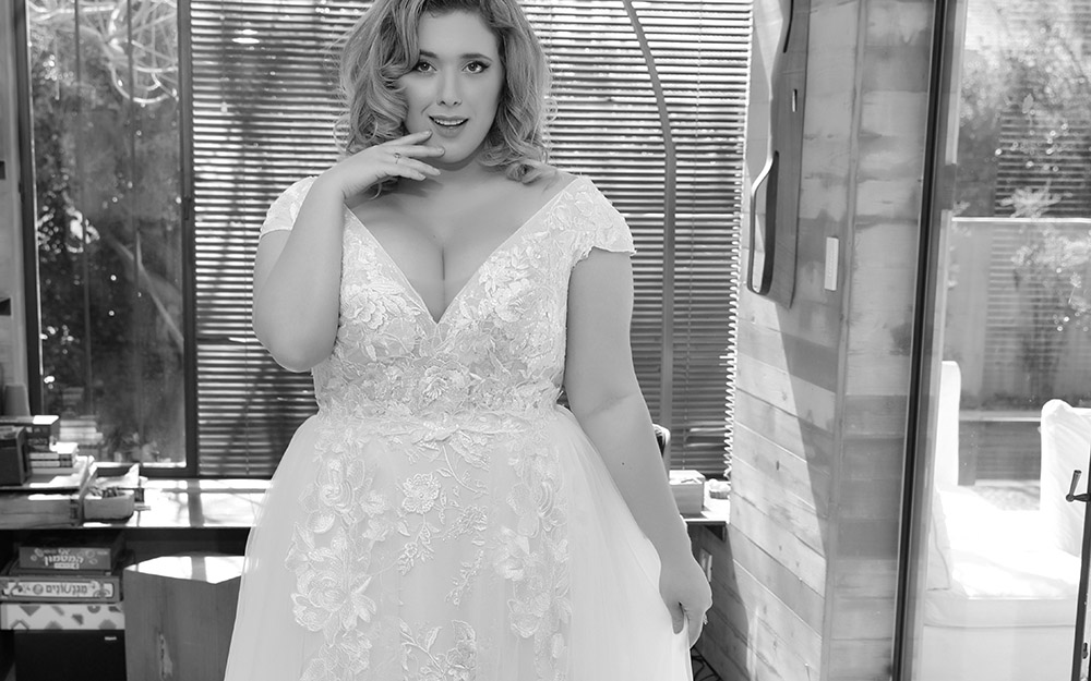 לנה מבית סטודיו לבנה, שמלת כלה במידה גדולה עם תרה מחשוף וי ושרווול קצר עם חצאית טול ותחרה בעלת שובל ארוך