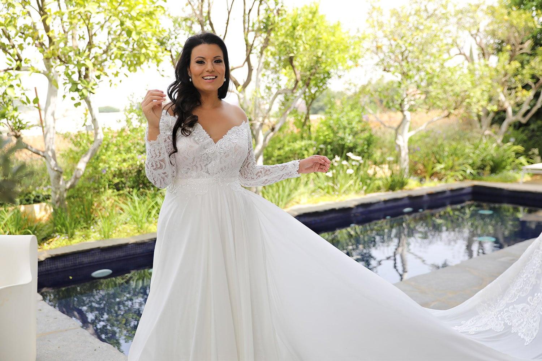 לידה מבית סטודיו לבנה שמלת כלה מתחרה עם מחשוף פתוח ושרוולי תחרה עם חצאית לחופה עם שובלארוכים