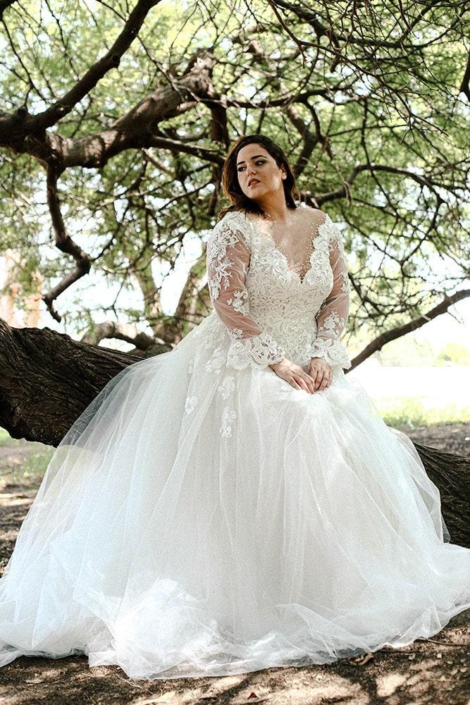 שמלת כלה מידה גדולה עם חלק עליון של תחרה ופנינים, שרוול ארוך וחצאית נפוחה ומנצנצתת. לוטי של סטודיו לבנה