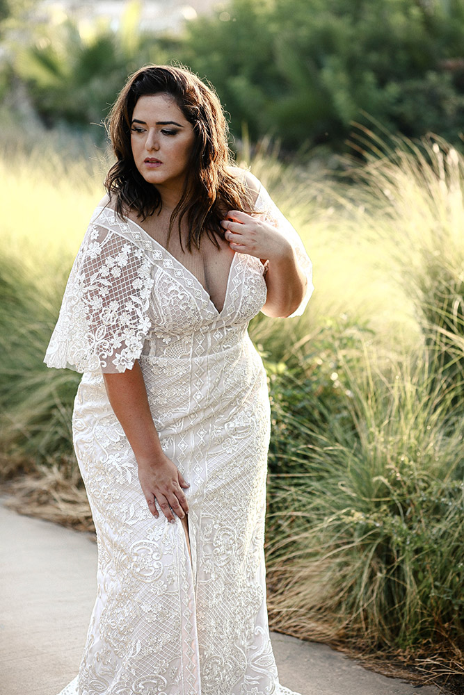 Luna by studio levana fitted all lace wedding dress with slit skirt and big v nackline . and bell cut sleeves