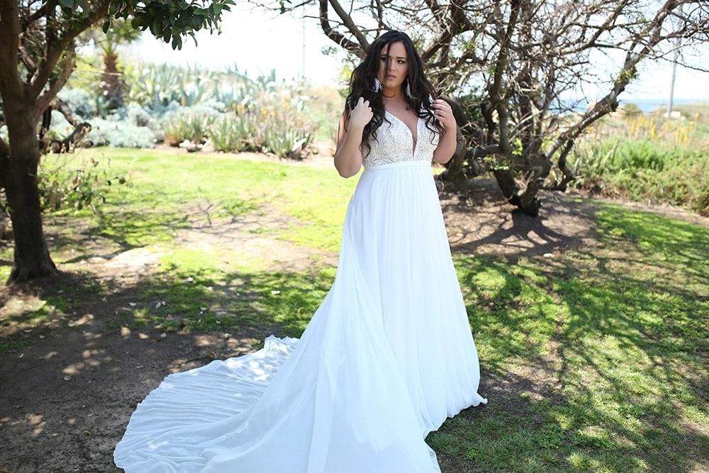 שמלת כלה בוהו שיק במידה גדולה עם תחרה גאומטרית מחשוף עמוק וחצאית נשפכת נקיה