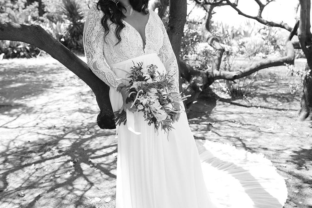 שמלת כלה בוהו שיק במידה גדולה עם תחרה גאומטרית מחשוף עמוק, שרוול ארוך וחצאית נשפכת נקיה