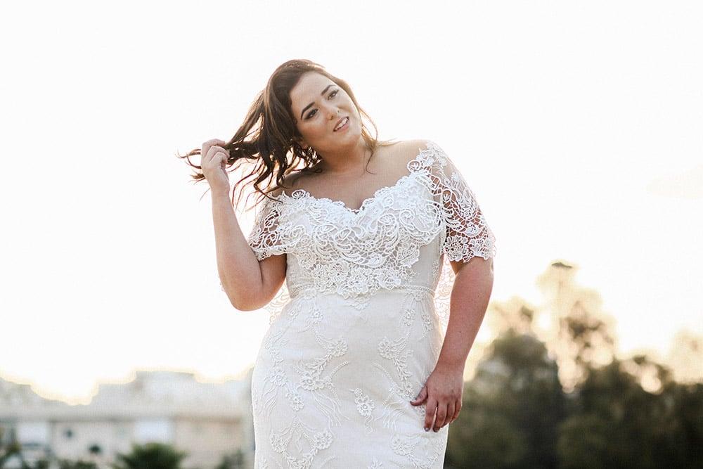 שמלת כלה צמודה במידה גדולה עם שרוול תחרה בצורת שכמייה , חגורה מחורזת ושובל ארוך . פייזלי מבית סטודיו לבנה