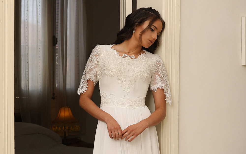 סאניס מבית סטודיו לבנה שמלת כלה צנועה עם שרוול תחרה קצר תחרה עדינה וחצאית נקיה