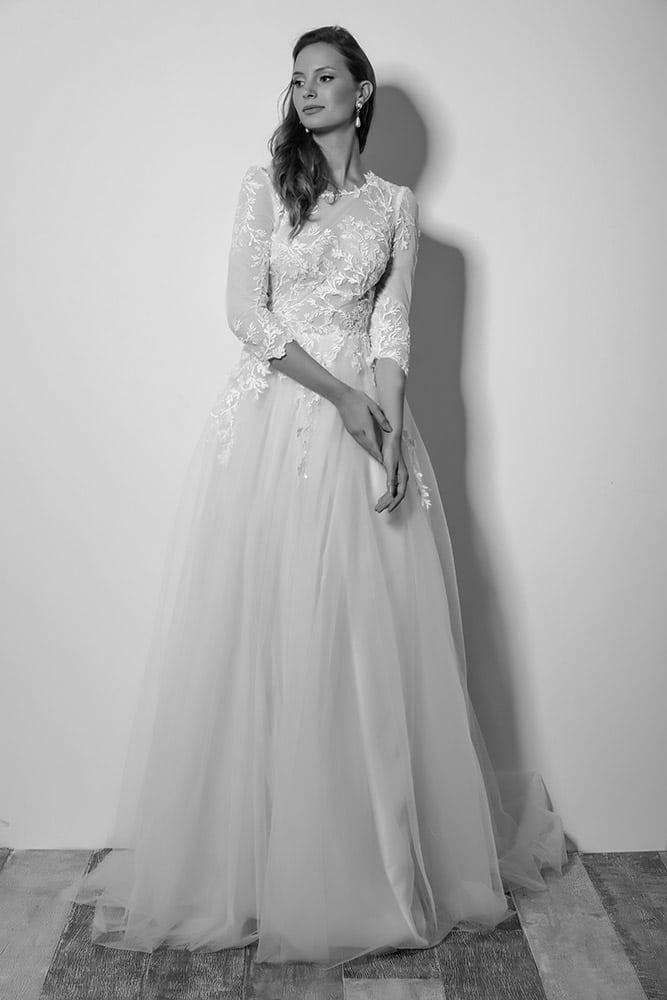 סרינה מבית סטודיו לבנה שמלת כלה צנועה עם חלק עליון של תחרה מחורזת ושרוול 3/4 וחצאית טול נסיכותית