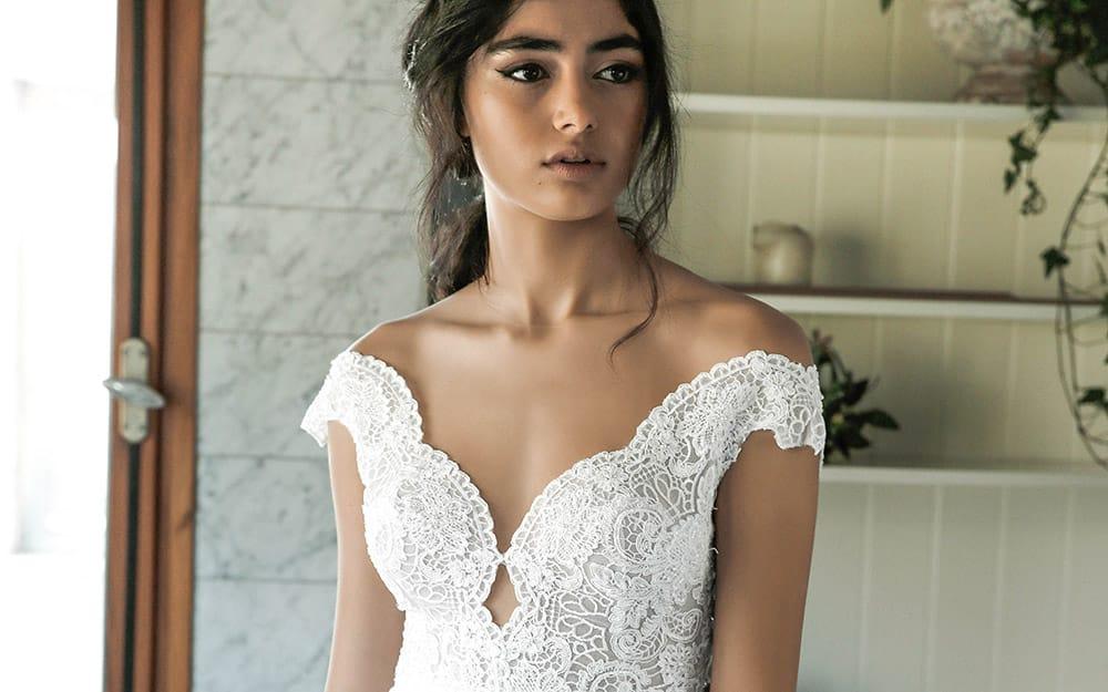 שירה מבית סטודיו לבנה שמלת כלה מתחרה עדינה עם מחשוף וכתפיים נופלות