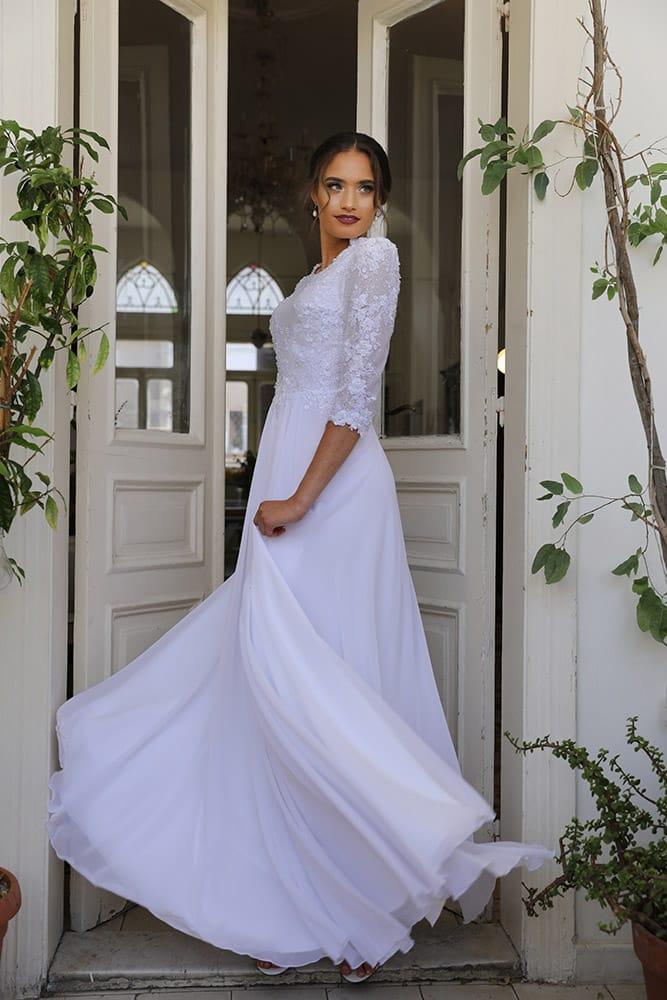 טוליפ מבית סטודיו לבנה, שמלת כלה צנועה עם חצאית טול נפוחה ותחרה עשירה